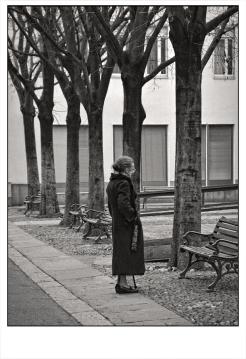 Anziana che parla con persone immaginarie sedute sulla panchina.